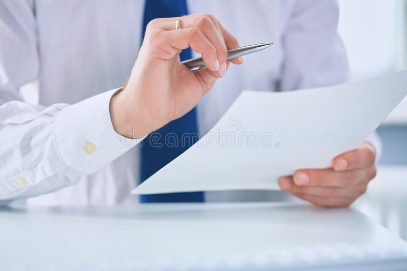 Serious business man working on documents and makes notes with a pen close-up. royalty free stock photos