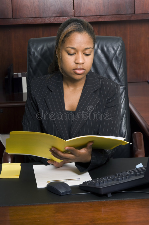 A serious business matter. African-american business woman reads a file in her office royalty free stock photos