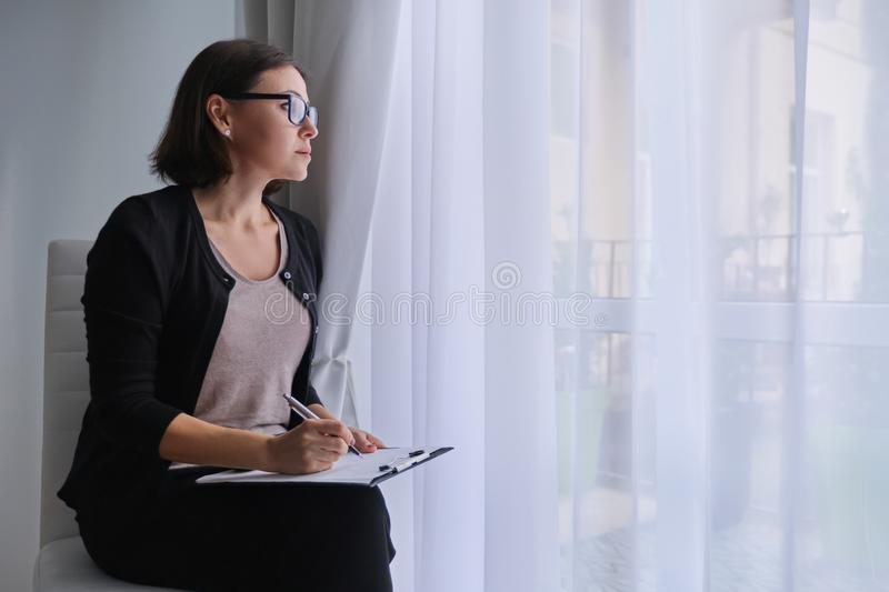 Serious business mature woman with clipboard sitting near the window royalty free stock photos