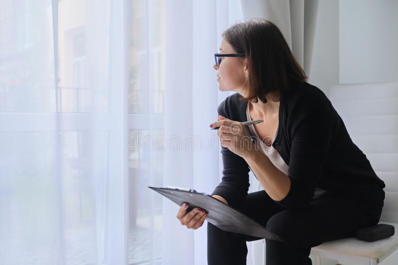 Serious business mature woman with clipboard sitting near the window stock photography