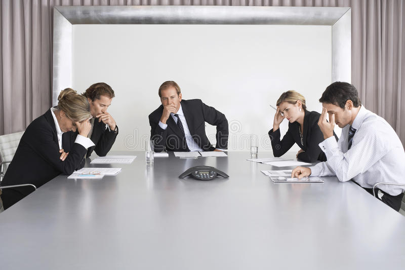 Serious Business People On Conference Call. Group of serious business people on conference call in boardroom royalty free stock images