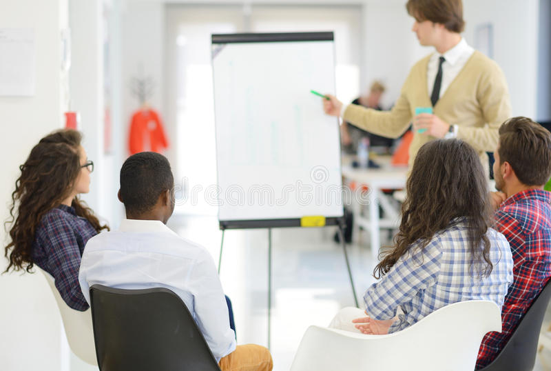 Serious business team with flip board in office discussing something royalty free stock photos