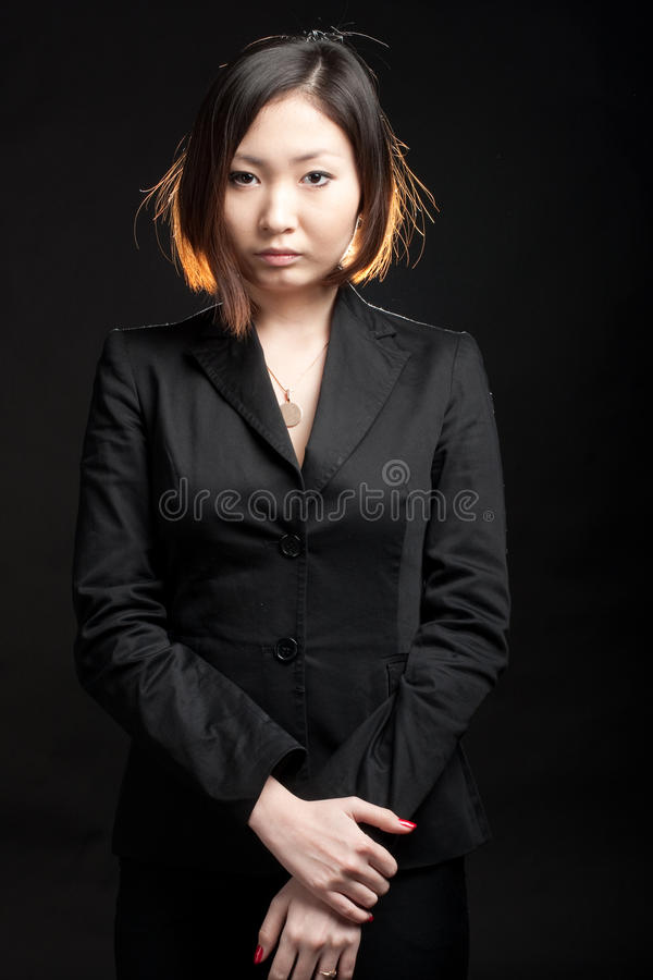 Serious business woman. Portrait of asian business woman isolated on black stock image