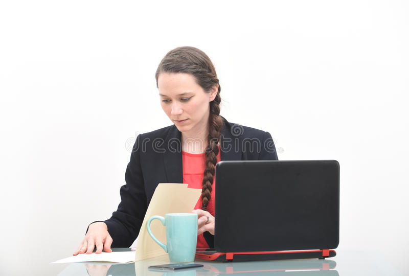 Serious business woman looking at document in files stock images