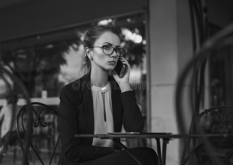 Serious business woman in suit talking on the cellphone. Serious business woman in elegant suit and glasses talking on the cellphone sitting in the outdoor cafe stock images