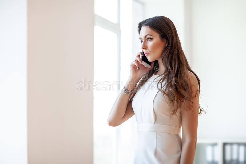 Serious business woman talking on smartphone in office royalty free stock photo