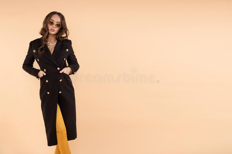 Serious business woman in black coat and glasses posing. Serious business woman wearing black coat and glasses posing on isolated background. Sexy adorable lady royalty free stock photography