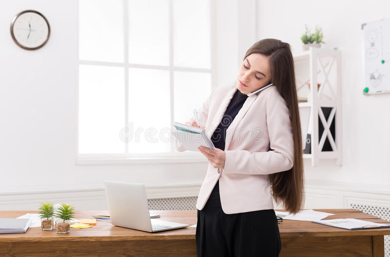Serious business woman at work talking on phone royalty free stock photo