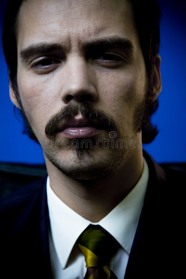 Serious Businessman. A close up portrait of a serious, determined, no-nonsense businessman with a moustache royalty free stock image