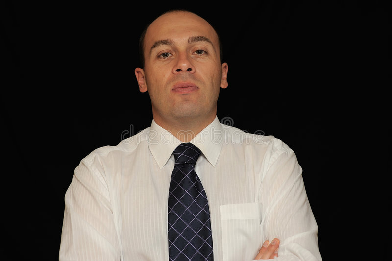Serious businessman. A portrait of a serious looking businessman, on a black studio background royalty free stock photo