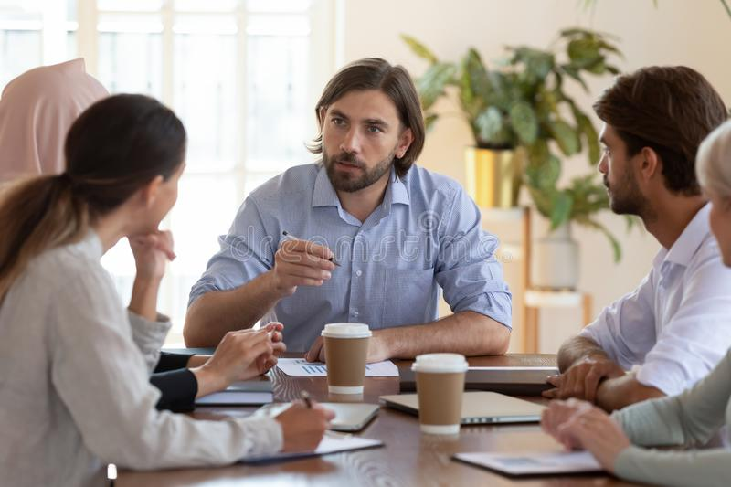 Serious businessman boss speaking at group briefing sit at table. Serious businessman boss ceo speaking at multicultural group briefing sit at conference table royalty free stock photography