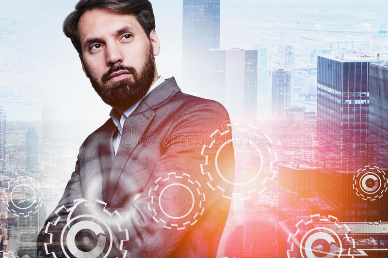 Serious businessman in city, gears. Serious bearded manager standing in city with double exposure of gears. Concept of leadership and well organized company stock photography