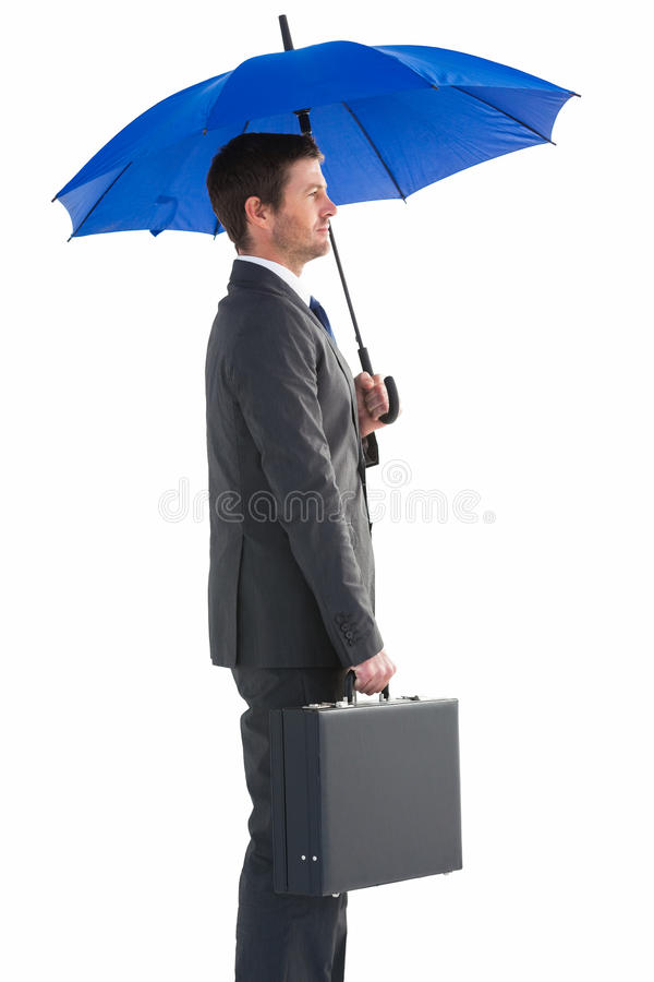 Serious businessman holding his umbrella and briefcase royalty free stock images