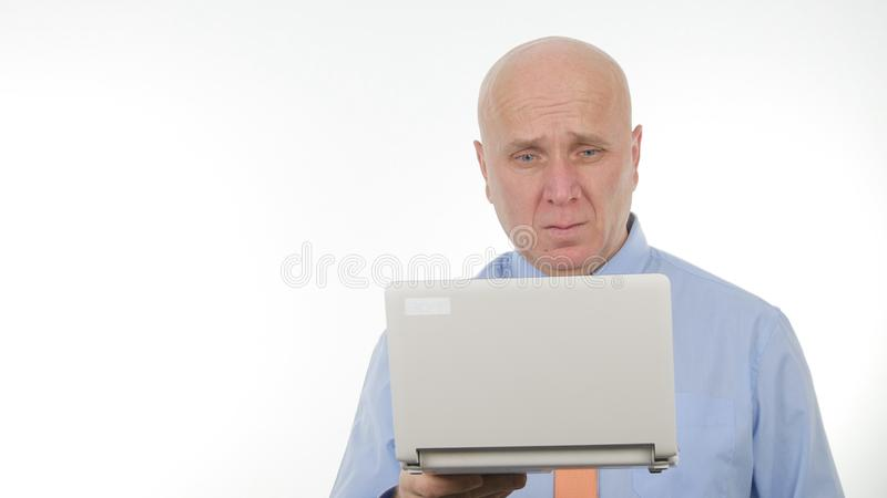 Serious Businessman Image Reading Bad Financial News on Laptop stock image