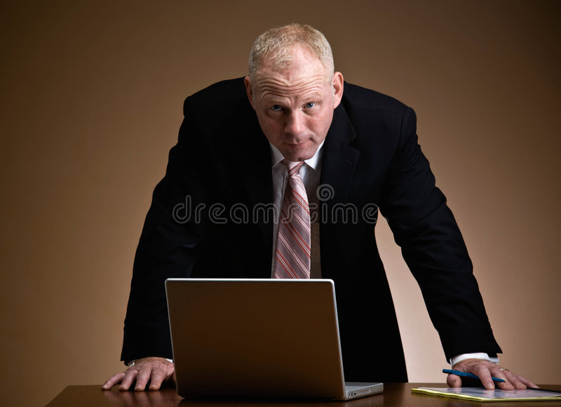 Serious businessman leaning over laptop stock photos