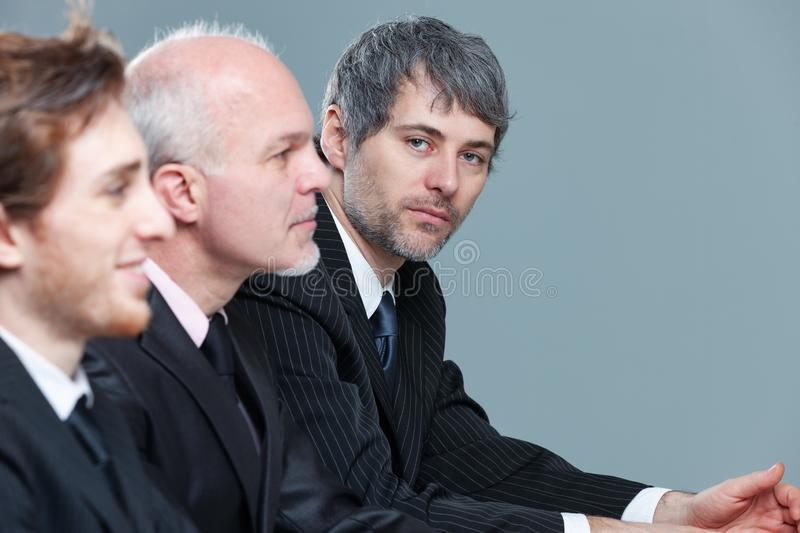 Serious businessman in a meeting with colleagues. Serious businessman in a meeting with two colleagues turning to look thoughtfully at the camera with focus to royalty free stock images