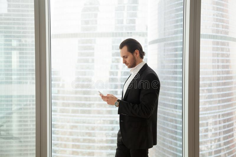 Serious businessman in modern office near window looking at cell royalty free stock image