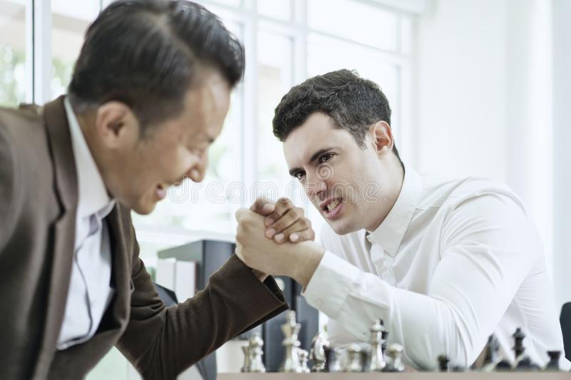 Serious businessman playing board chess game together, Competition and Strategy planning success ideas. Chess board game concept.  royalty free stock photos