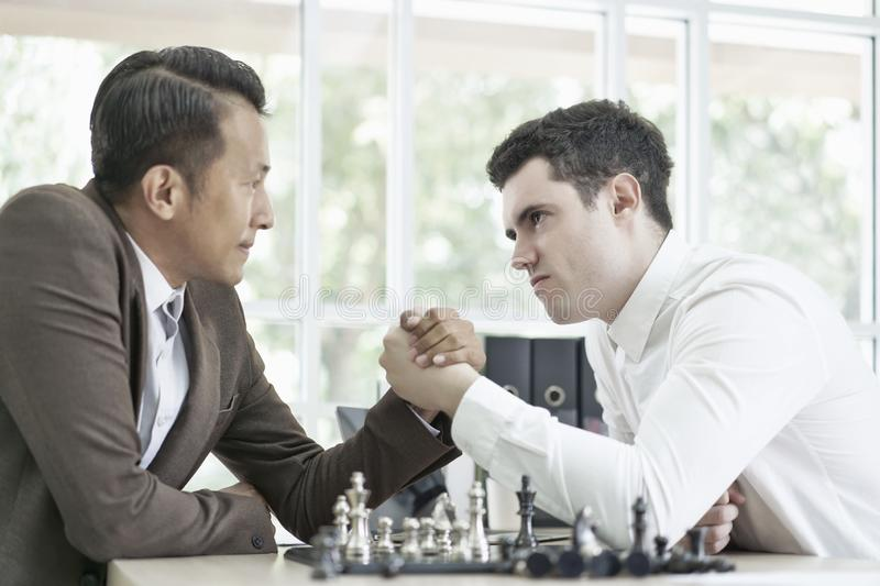 Serious businessman playing board chess game together, Competition and Strategy planning success ideas. Chess board game concept stock photo