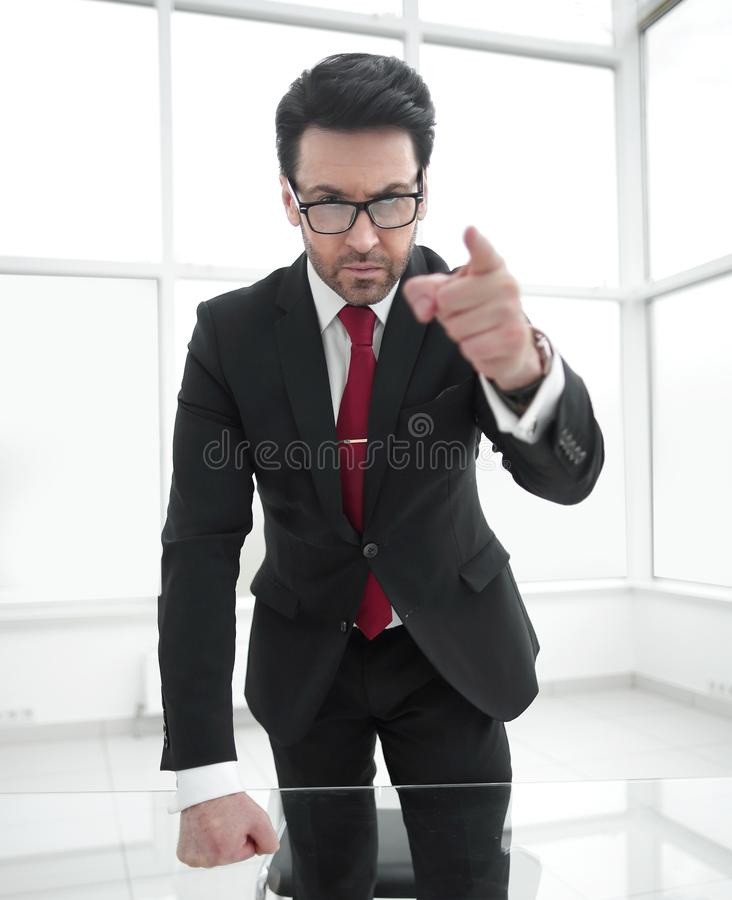 Serious businessman pointing his finger at you while standing in his office. stock photos