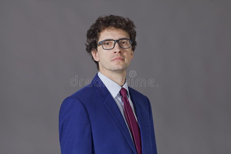 Serious businessman portrait. Young man wearing blue suit and glasses. stock image