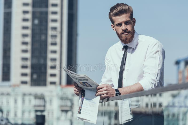 Serious Businessman Reading Newspaper Outdoor stock photo