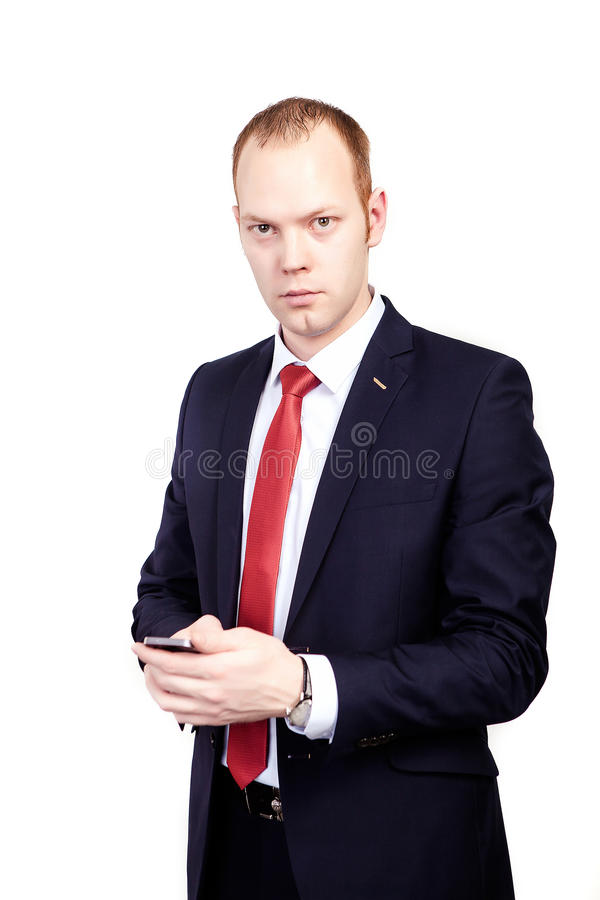 Serious businessman reading text message on smart phone against. White background stock photography