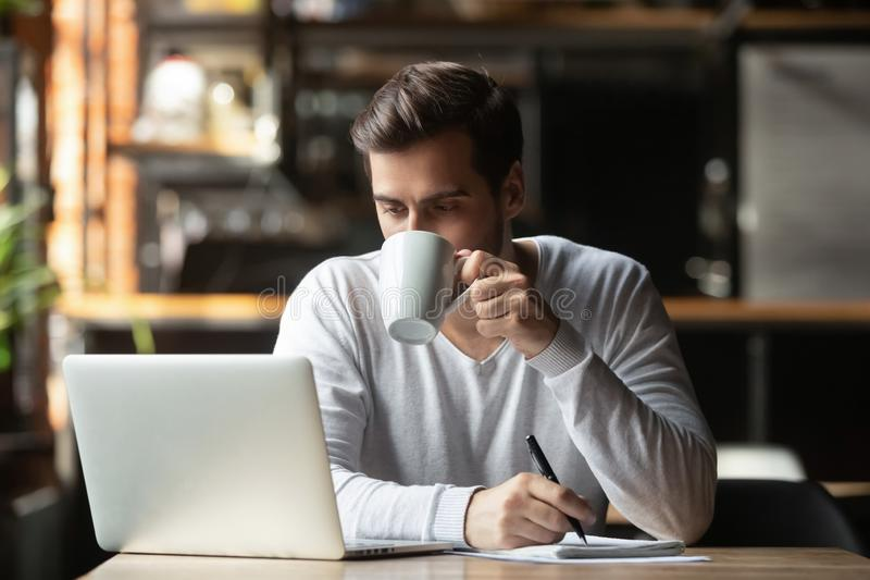 Serious businessman sitting in coffeehouse drinking coffee looking at computer royalty free stock photos