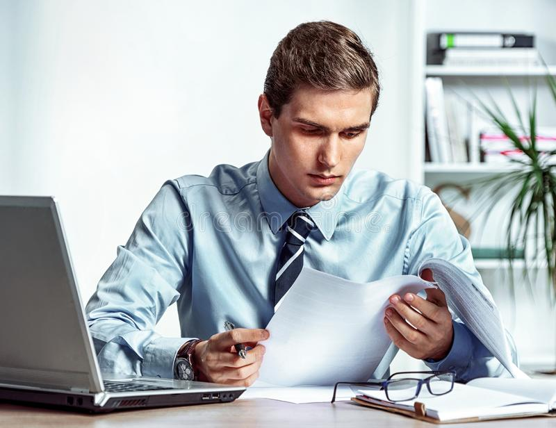 Serious businessman sitting at his desk reading a documents royalty free stock photo