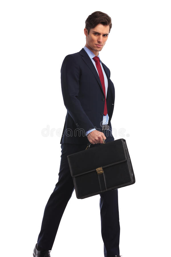 Serious businessman in suit and tie holding a briefcase royalty free stock photography