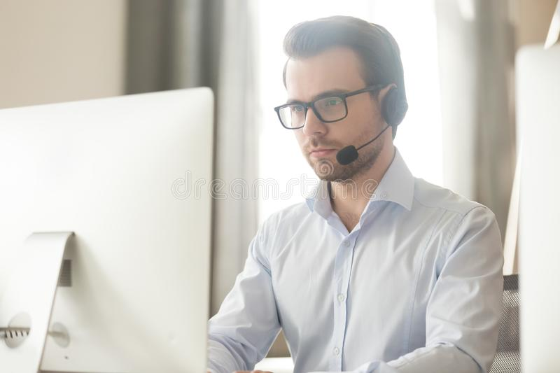 Serious businessman talking with headset on computer making conference call. Serious businessman manager talking with headset on computer making business stock image