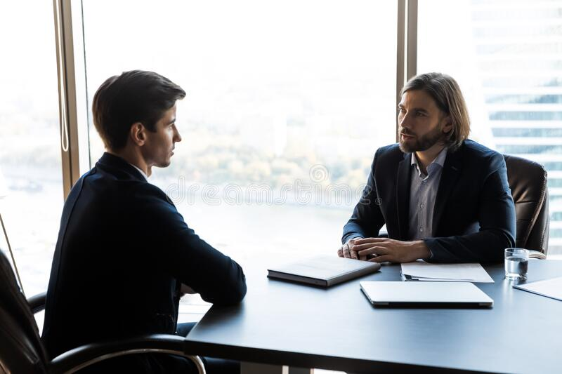 Serious businessman talking with mentor coach lead in office. royalty free stock photos