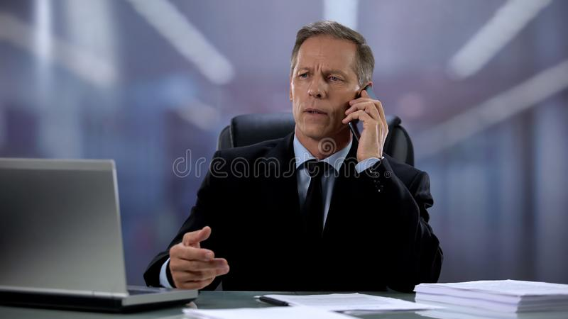 Serious businessman talking on phone with business partner, setting meeting stock photo
