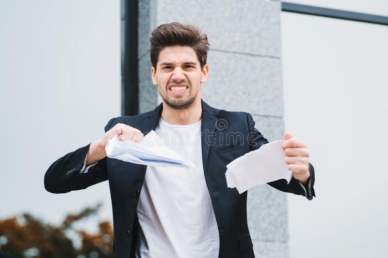 Serious businessman tearing contract in pieces. Angry furious male office worker throwing crumpled paper, having nervous royalty free stock images