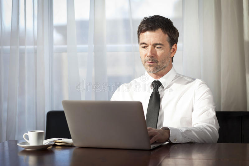 Serious Businessman teleworking. On a Laptop. stock image