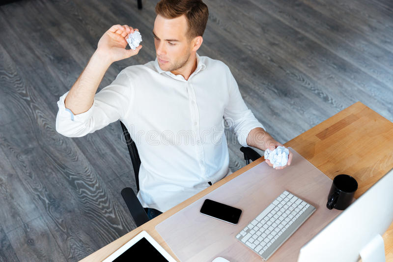 Serious businessman throwing crumpled paper and working in office royalty free stock photo