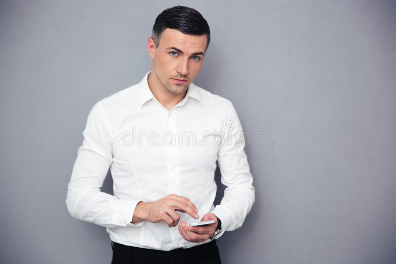 Serious businessman using smartphone. And looking at camera over gray background royalty free stock images