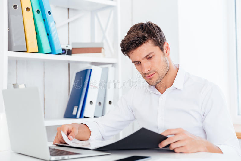 Serious businessman working with documents in folder at workplace. In office royalty free stock images