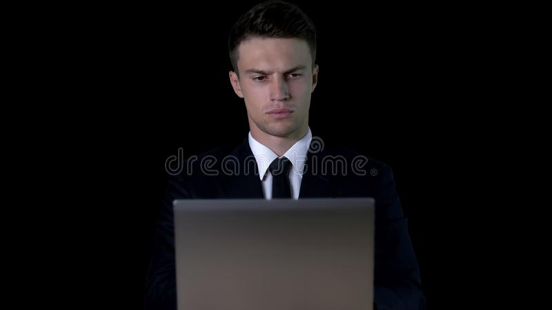 Serious businessman working on laptop against dark background, confidence royalty free stock image