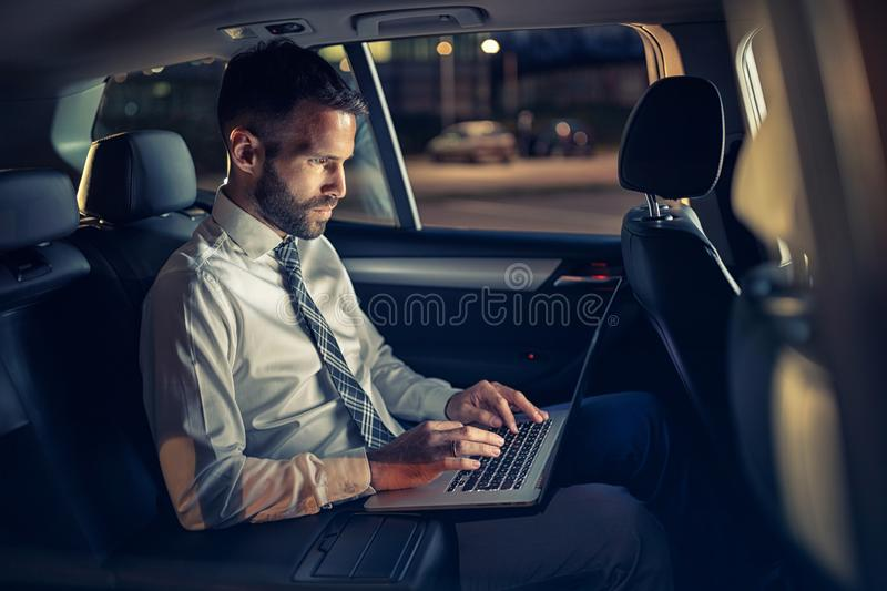 Serious businessman working late in car on laptop. In back seat stock image