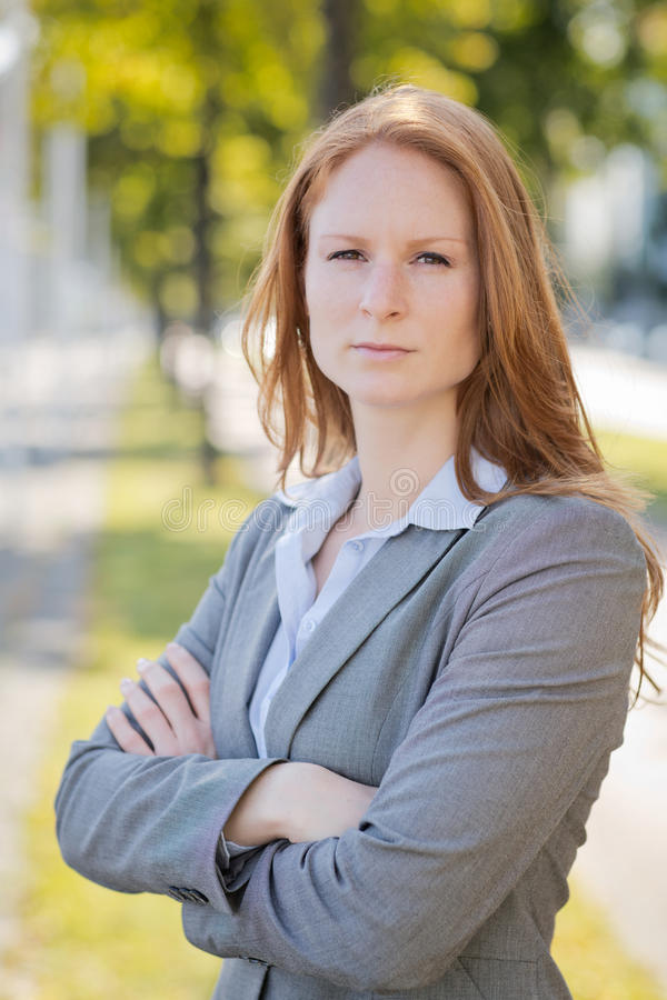 Serious Businesswoman in a City. Young and confident businesswoman poses for a portrait in a city environment stock image