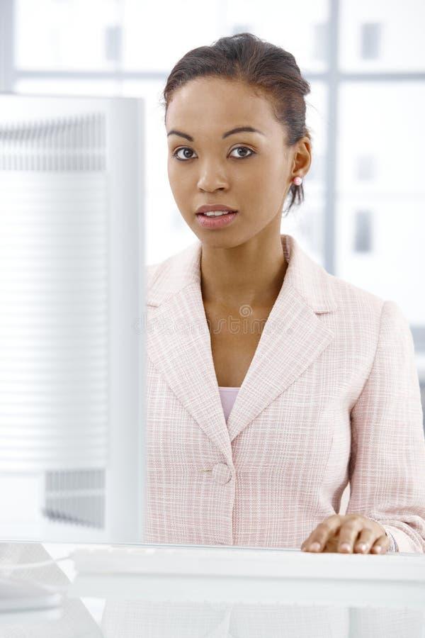 Serious businesswoman at desk. Portrait of serious businesswoman sitting at office desk stock photo