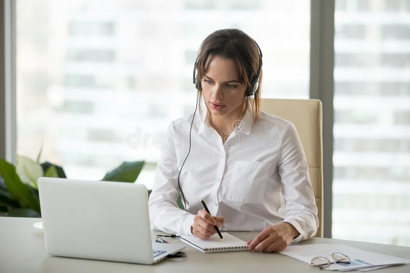 Serious businesswoman in headphones watching webinar on laptop m royalty free stock photos