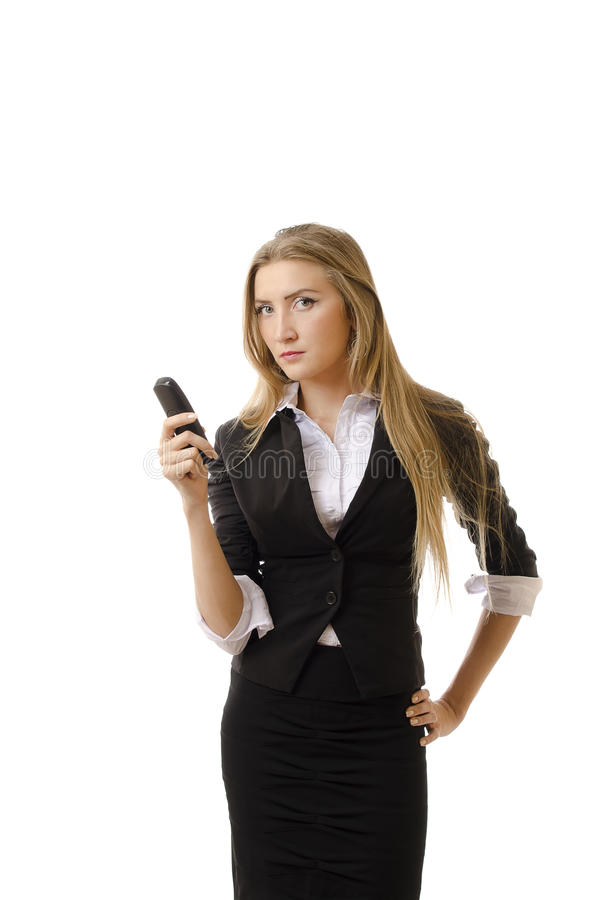 Serious Businesswoman Holding Cell Phone. Portrait of a serious Caucasian businesswoman holding cell phone with hand on hip over white background. Vertical shot stock photography