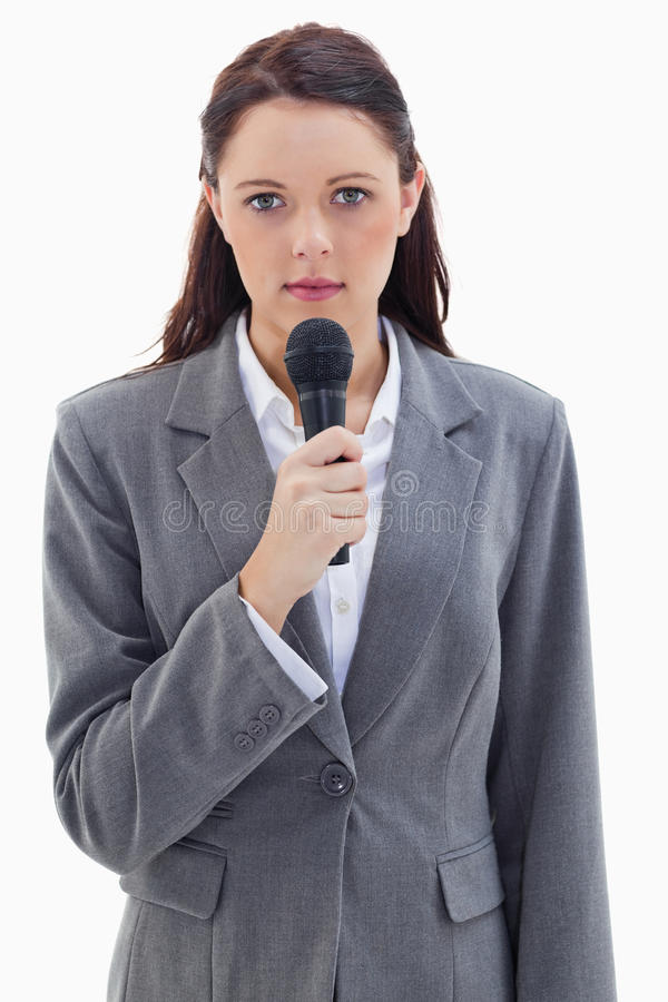 A serious businesswoman holding a microphone stock photos