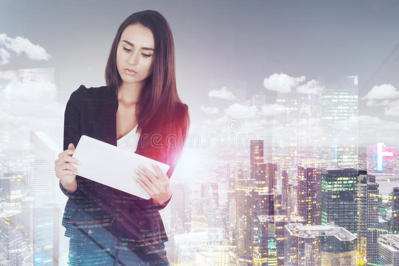 Serious businesswoman with tablet in city stock photo