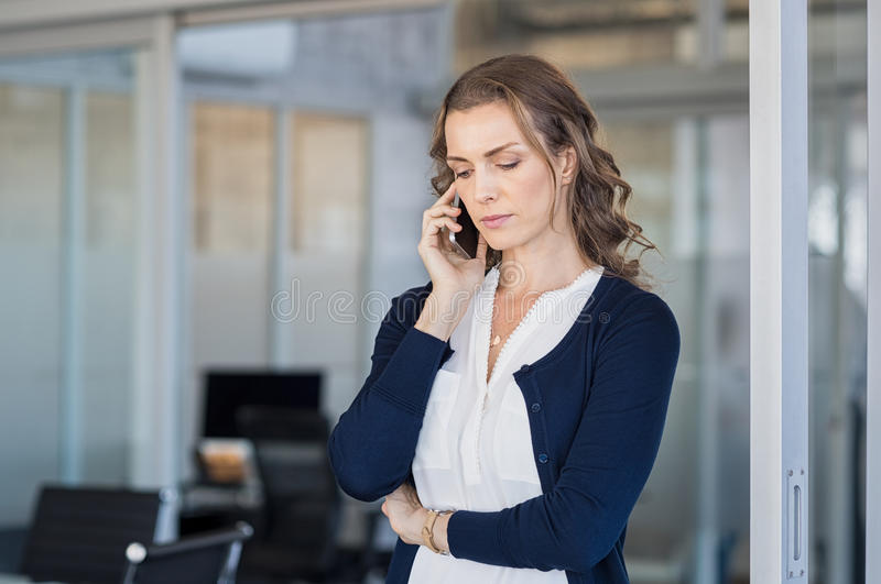 Serious businesswoman talking on phone royalty free stock photography