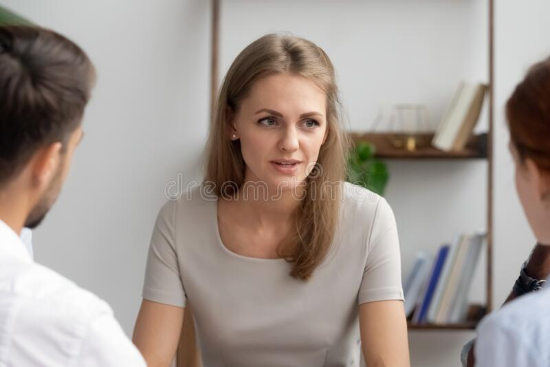 Serious businesswoman, team leader holding briefing with employees stock image