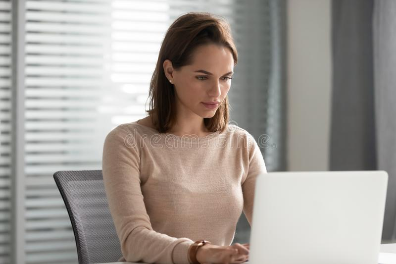 Serious businesswoman using laptop, looking at screen, working on project royalty free stock image