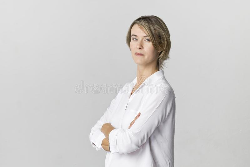 Serious businesswoman in white shirt portrait against white wall stock photo